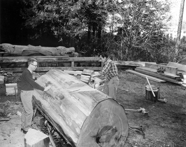 Bill Reid and Doug Cranmer carving cedar log in Totem Park, 1961