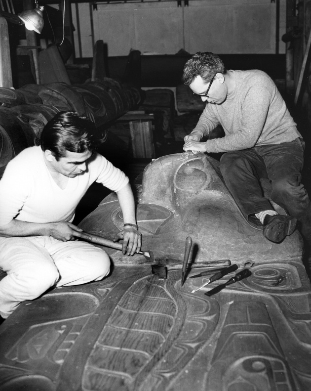 Bill Reid and Doug Cranmer carving the frontal board of Haida Mortuary pole, 1961