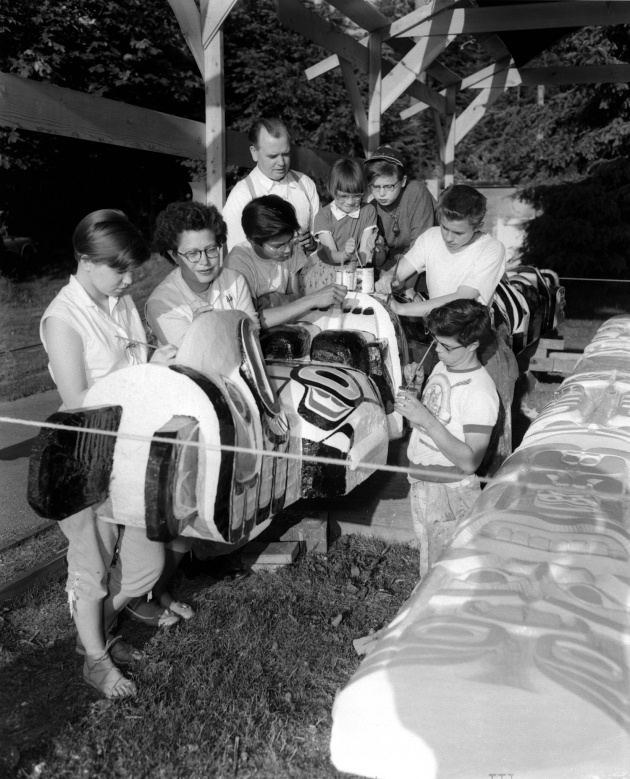 Ellen and Ted Neel and children carving a totem pole, 1955