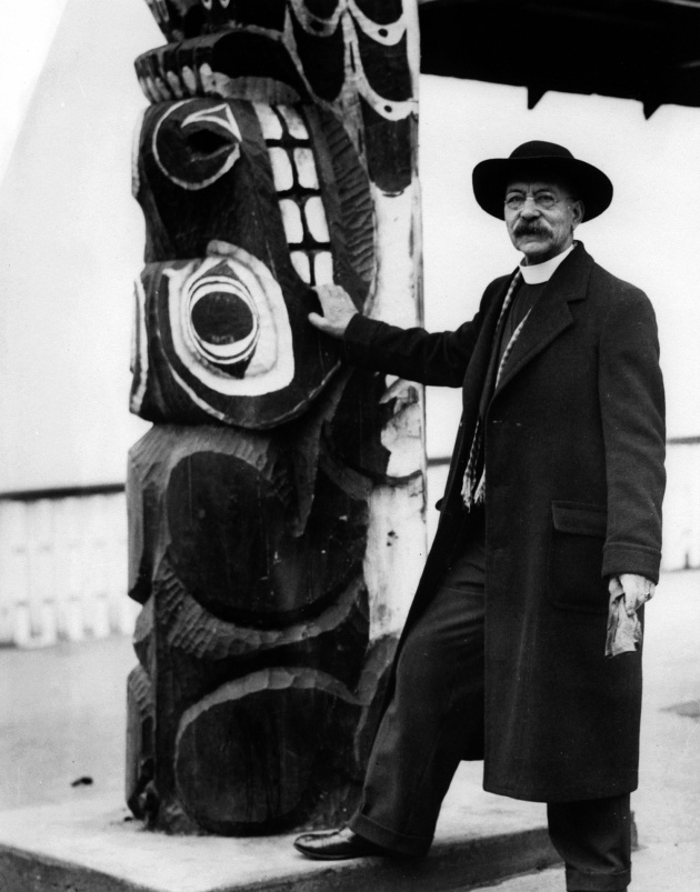 Dr Rally beside a totem pole, circa 1940